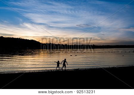 Silhouette Of Two Kids Near The Lake At Sunset