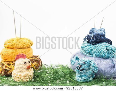 knitting toy rabbit and chicken on a background of thread grass