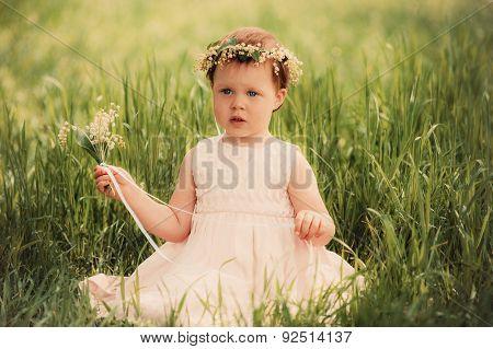 beautiful little girl in wreath of flowers