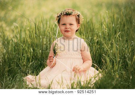 Little girl smiling, child sitting on the grass