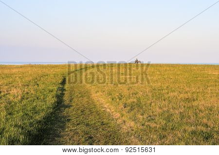 Field With A Mown Path And A Bench On A Horizon