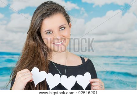 brunette holding an origami heartshaped paper figure in front of oceanic cloud background