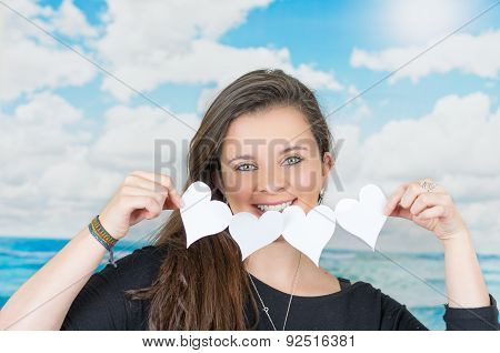 brunette holding an origami paper figure in front of oceanic cloud background