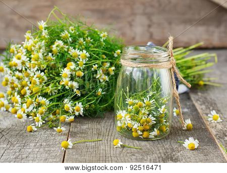 Chamomile Flowers In A Glass Jar On A Wooden Background