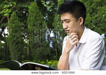 Libros de lectura de joven estudiante en el Parque de la escuela