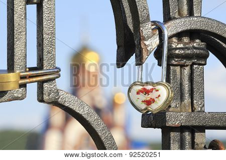 Bride And Groom Hang A Padlock On The Bridge Near The Church As A Sign Of Love And Fidelity