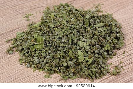 Heap Of Dried Green Marjoram On Wooden Background