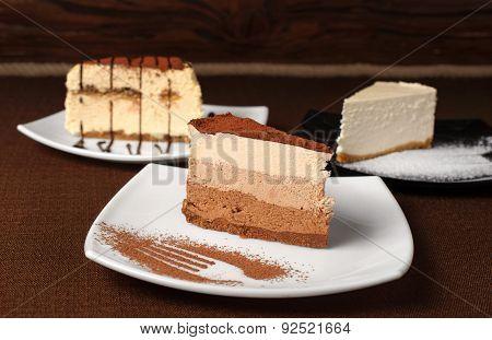 Tiramisu And Chocolate Cheesecake On A Dark Background
