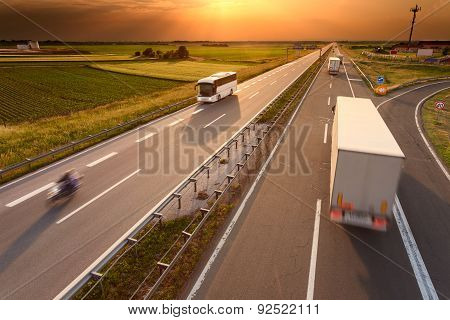Truck Bus And Motorcycle On Motorway At Sunset