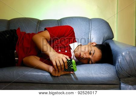 Teen using a smartphone while lying down on a couch and smiling