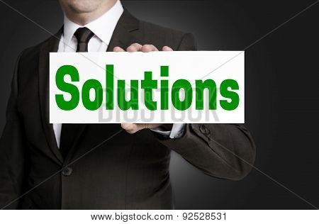 Solutions Sign Is Held By Businessman