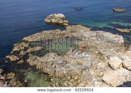 Vacationers Sunbathing On The Rocky Coast Of Sevastopol
