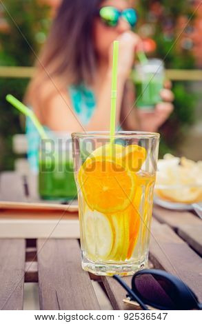 Infused fruit water cocktails and woman drinking green smoothie
