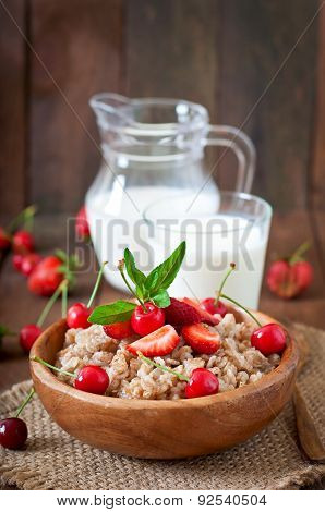 Oatmeal porridge with berries in a wooden bowl