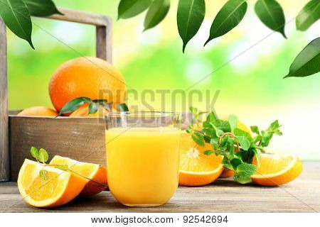 Glass of orange juice with oranges in crate on wooden table and natural background