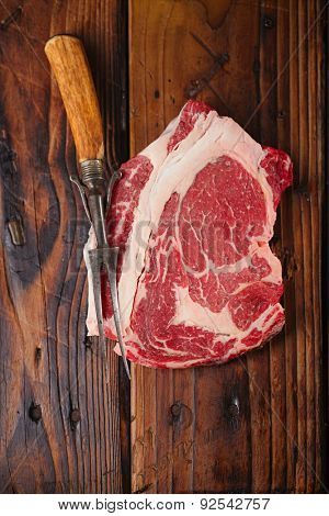 raw beef Ribeye  steak   on wooden  table with vintage carving fork