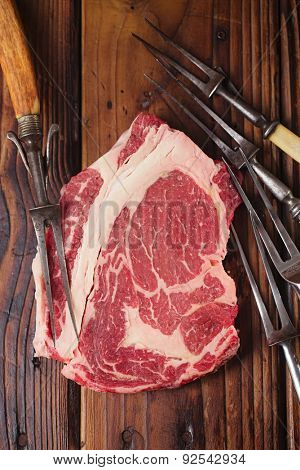 raw beef Ribeye  steak   on wooden  table with vintage carving forks