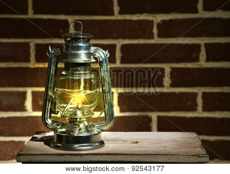 Burning kerosene lamp on brick wall background