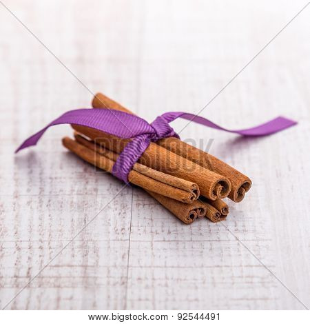 Cinnamon isolated on wooden background.