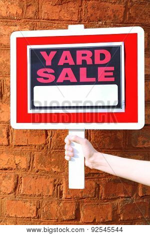 Wooden Yard Sale sign in female hand on red brick wall background