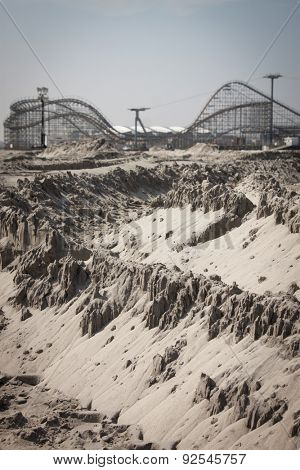 Sand dunes on a beach with a roller coaster in the background.