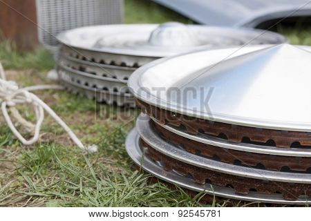 Stacks of vintage chrome hubcaps on the grass at a yard sale.