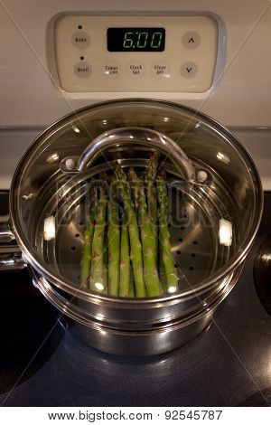 Green asparagus cooking on a stove in a stainless steel steamer pot.