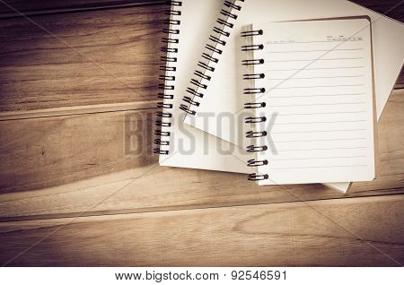 White notebooks laying on a wooden table - still life