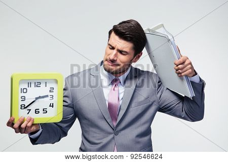 Disappointed businessman holding folders and clock over gray background