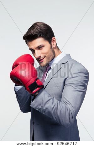 Businessman ready to fight with boxing gloves over gray background. Looking at camera