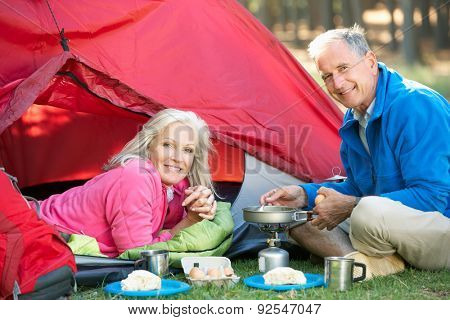 Senior Couple Cooking Breakfast On Camping Holiday