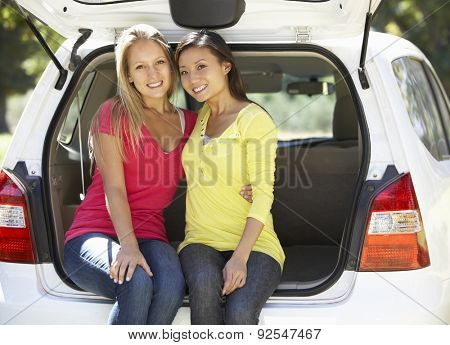 Two Young Women Sitting In Trunk Of Car