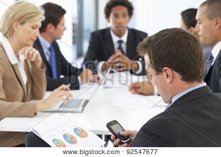 Businessman Checking Phone During Meeting In Office