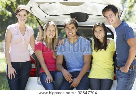 Group Of Young Friends Sitting In Trunk Of Car