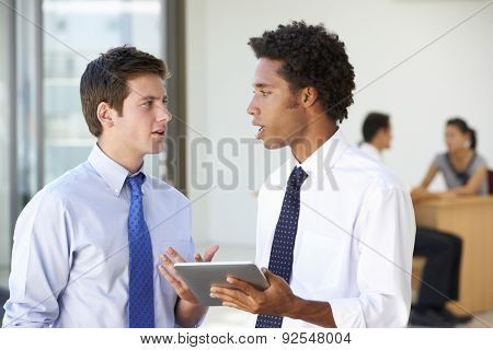 Two Male Executives Looking At Tablet Computer With Office Meeting In Background