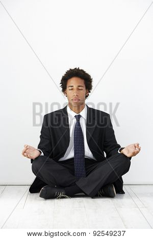 Studio Portrait Of Businessman Sitting On Floor Meditating