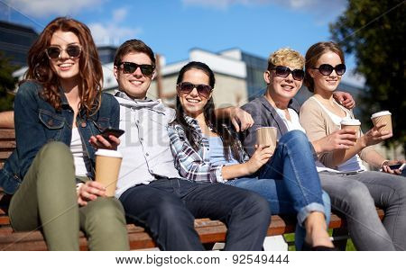 summer holidays, friendship, leisure and teenage concept - group of happy students or teenagers hanging out and drinking coffee at campus or park