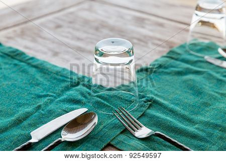 table setting, silverware and eating concept - close up of cutlery with glass and napkin on restaurant table