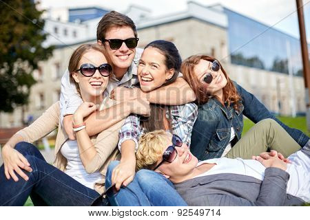 summer holidays, friendship, leisure and teenage concept - group of students or teenagers hanging out and hugging at campus or park