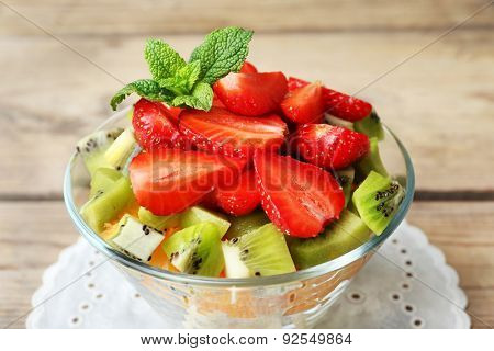 Dessert of fresh fruits in glass saucer on wooden table, closeup