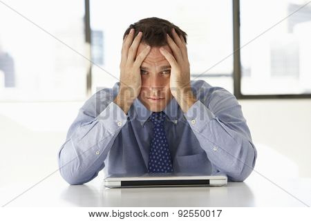 Frustrated Businessman Sitting At Desk In Office Using Laptop