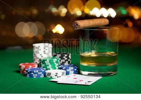 gambling, fortune and entertainment concept - close up of casino chips, whisky glass, playing cards and cigar on green table surface over holidays night lights background