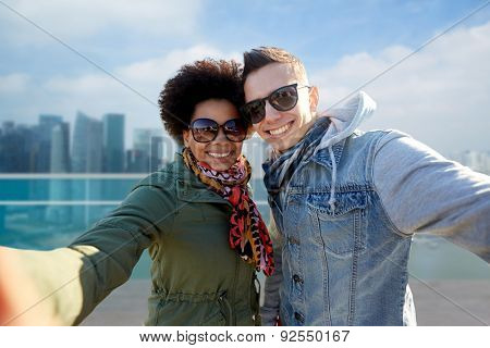tourism, travel, people, leisure and technology concept - happy international teenage couple taking selfie over singapore city background