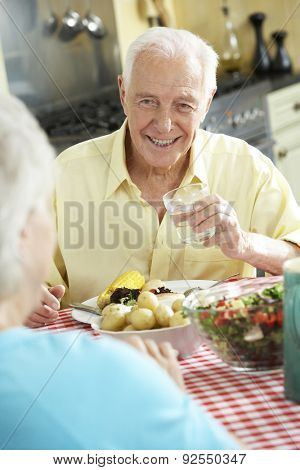 Senior Couple Eating Meal Together In Kitchen