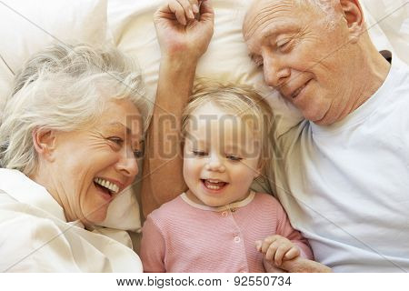 Grandparents Cuddling Granddaughter In Bed