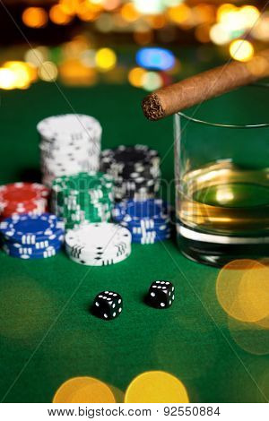 gambling, fortune and entertainment concept - close up of casino chips, whisky glass, dice and cigar on green table surface over holidays night lights background