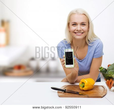 healthy eating, vegetarian food, dieting and people concept - smiling young woman cooking vegetables and showing blank smartphone screen over kitchen background