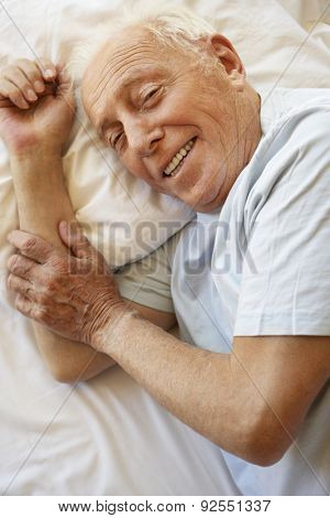 Senior Man Relaxing In Bed