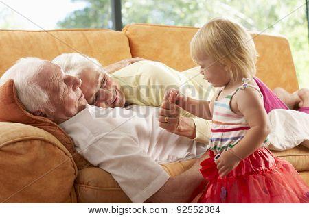 Senior Couple Lying On Sofa With Granddaughter