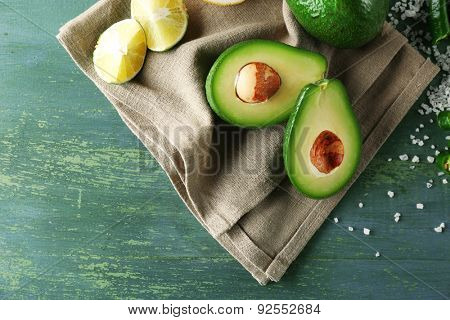 Sliced avocado, cucumber, pepper and lemon lime on wooden background